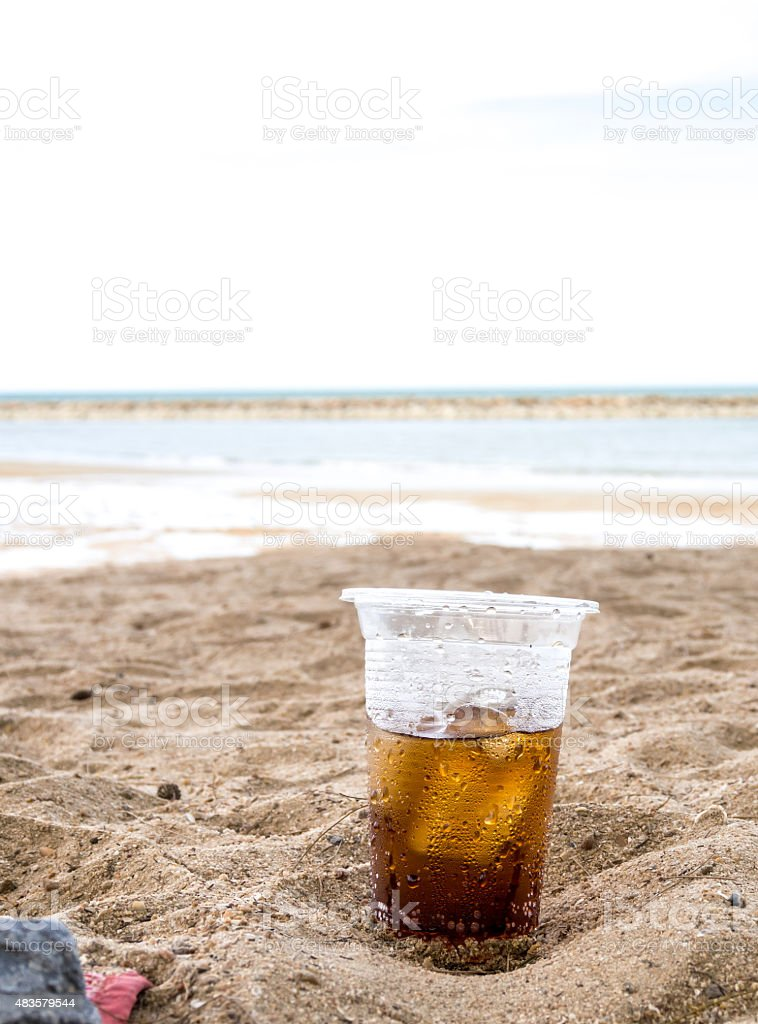 Glass plastic sparkling water in sand royalty-free stock photo