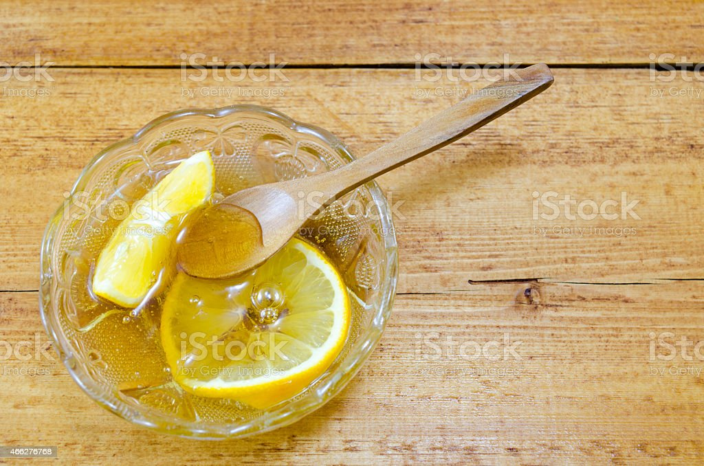 Glass plate filled with honey and lemon slices royalty-free stock photo