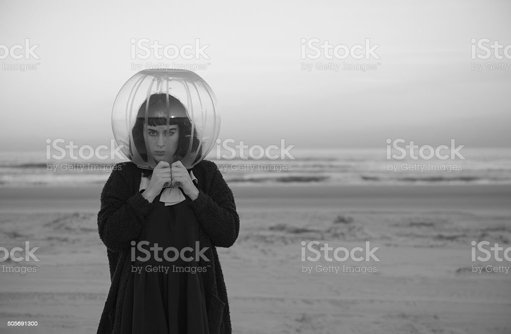Glass sphere coving woman head on coastline stock photo