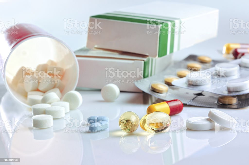 glass table with pills, blisters and containers stock photo