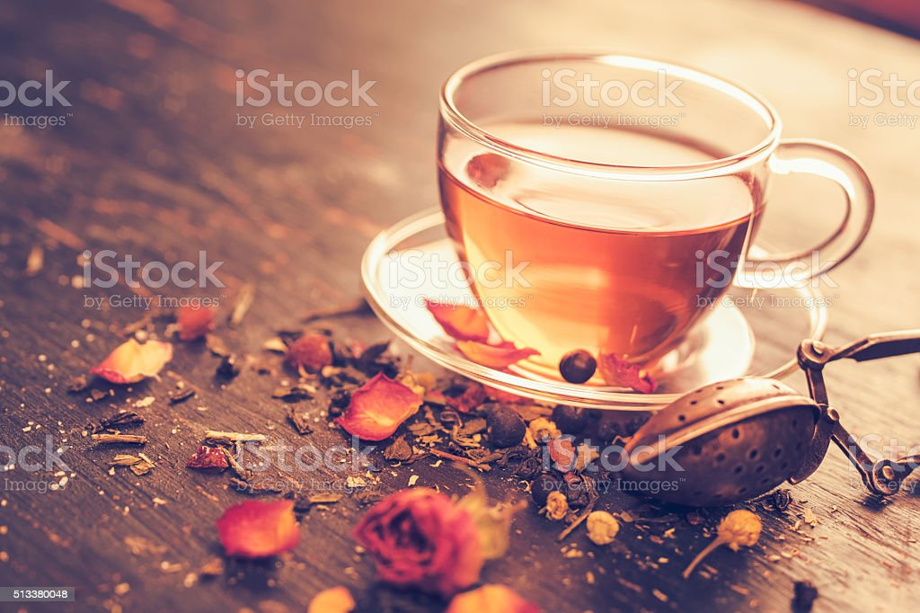 Glass tea cup with dry rosebuds stock photo