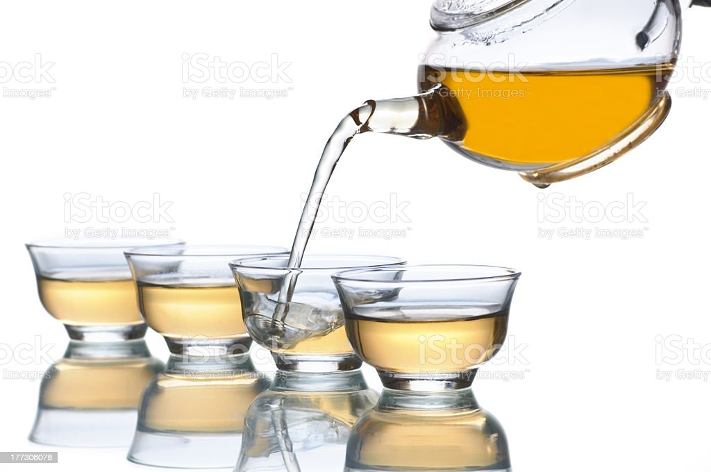 Glass tea kettle pouring tea into four clear lass cups  stock photo
