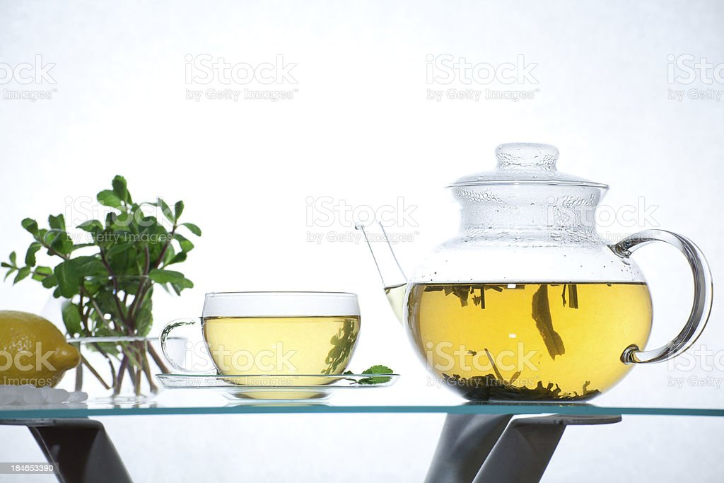 Glass teapot and cup with green herbal tea on table stock photo