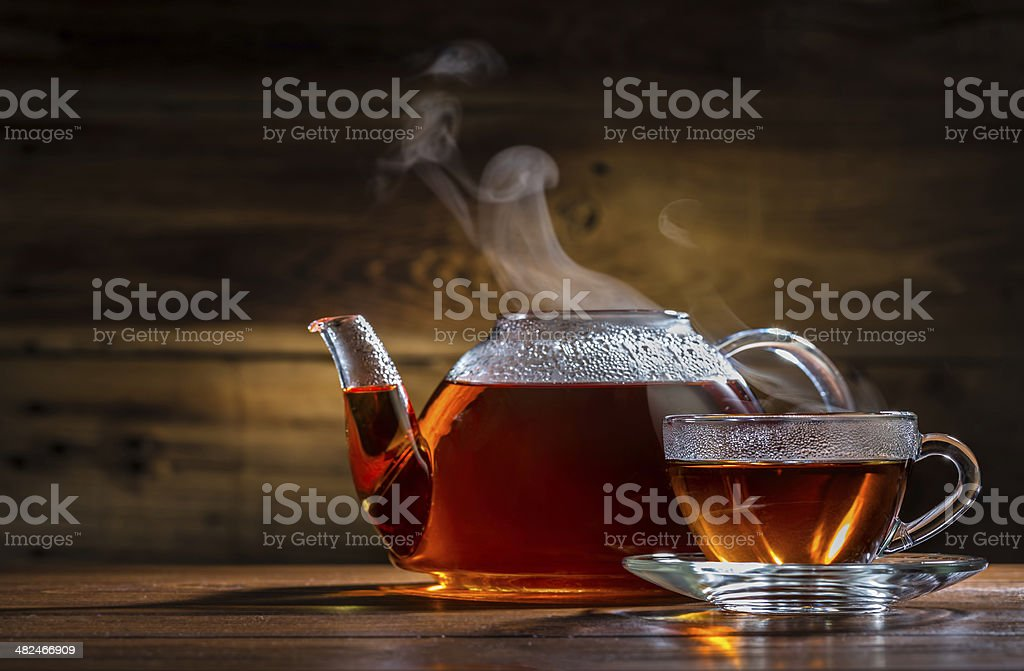 glass teapot and mug on the wooden background stock photo