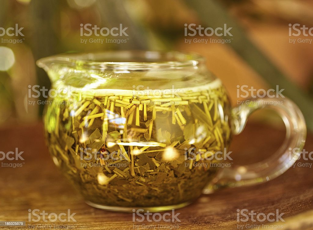 Glass teapot filled with herbal tea on a wooden tray royalty-free stock photo