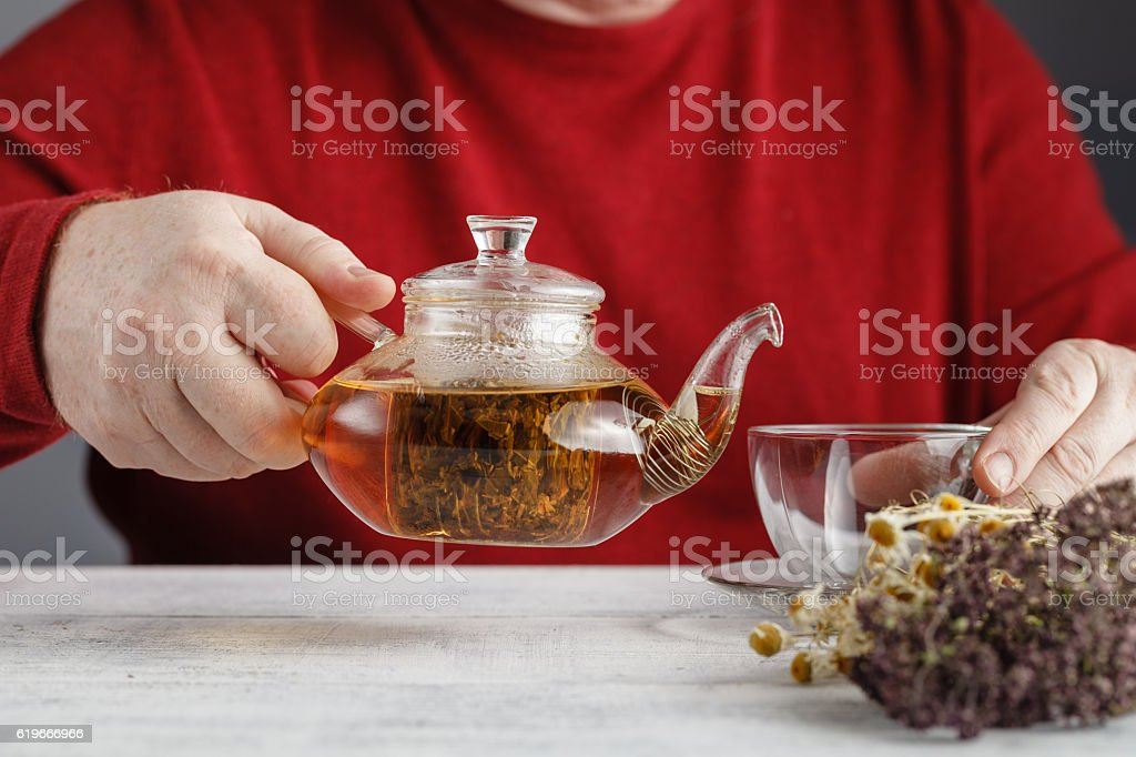 Glass teapot pouring black tea into cup stock photo
