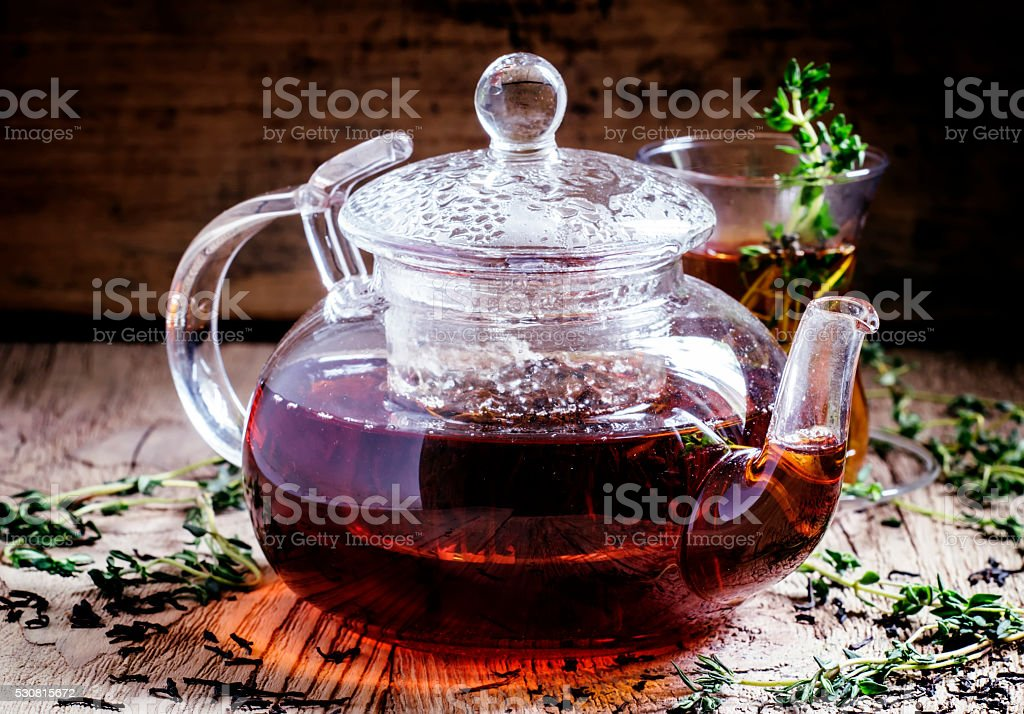 Glass teapot with black tea with thyme stock photo