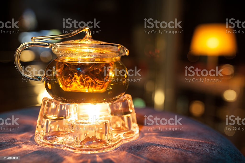 glass teapot with candle heater; stock photo