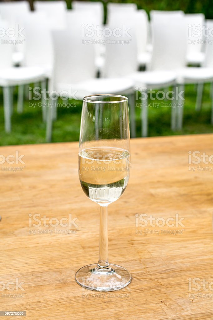 Glass to toast with rows of white chairs in backdrop stock photo