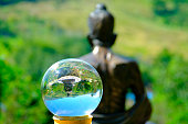 Glass transparent ball on back view of Buddha Statue.