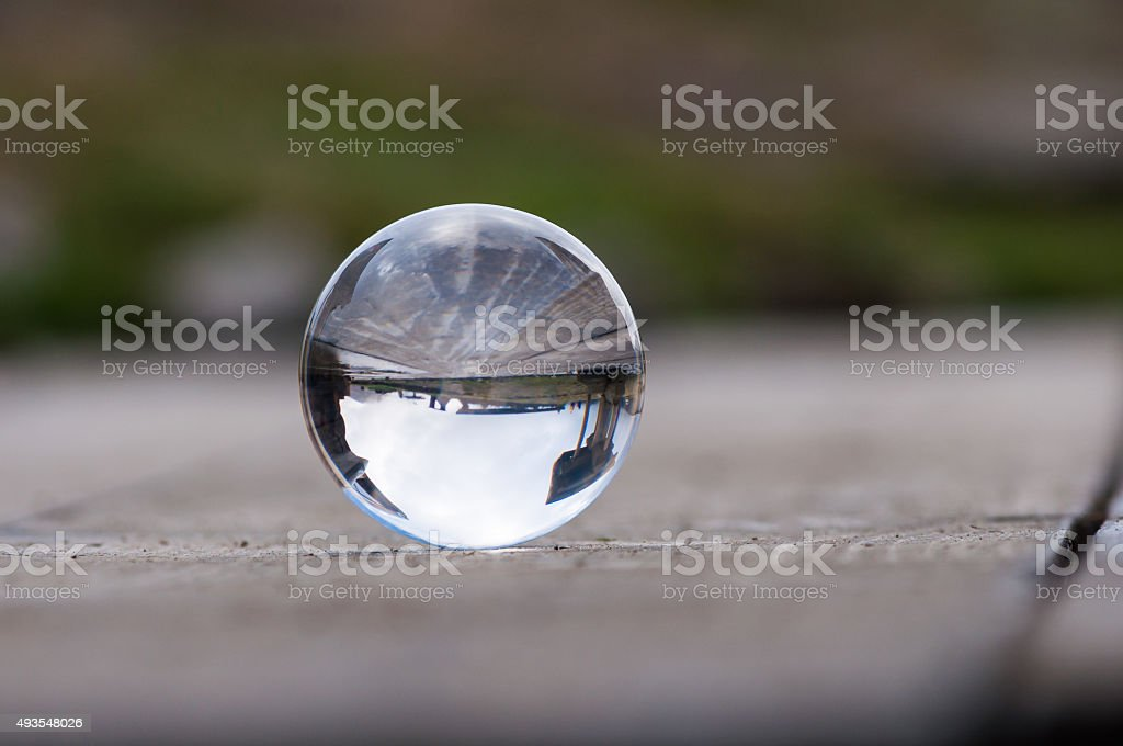 Glass transparent ball on dark green background and wooden surface stock photo