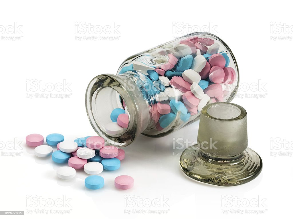 Glass vial with stopper and group a pill. royalty-free stock photo