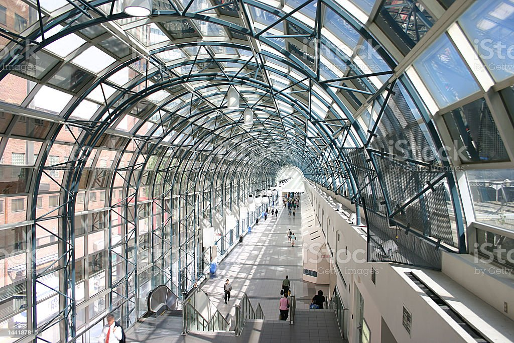 A glass walkway with people walking through it stock photo
