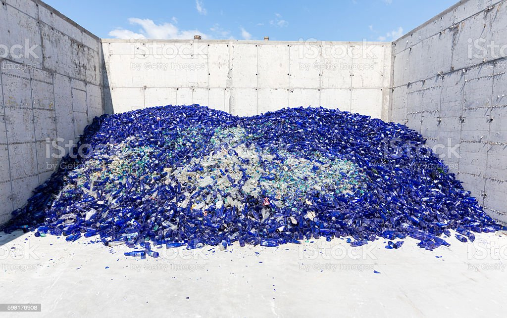 Glass waste in recycling facility. Blue bottles stock photo