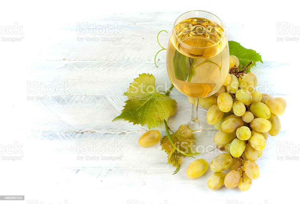 Glass white wine with grapes and leaf on wooden board stock photo