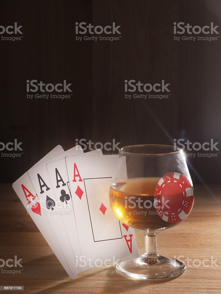 Glass with a alcohol , playing cards . wooden background stock photo