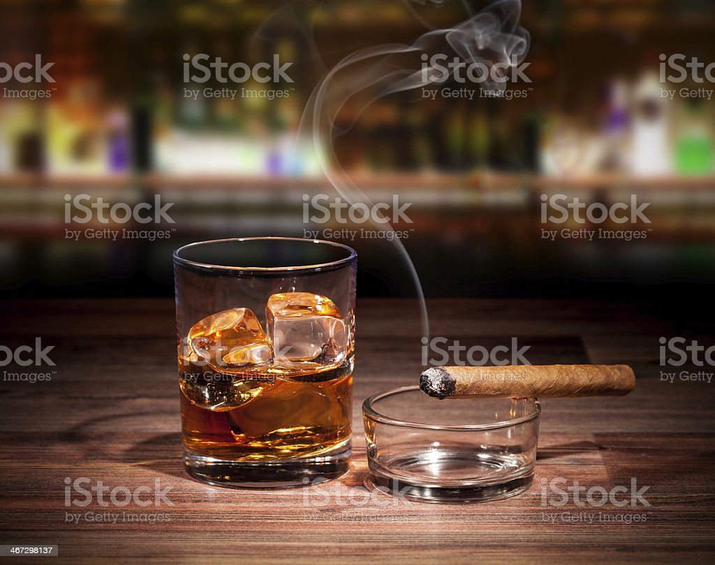 A glass with a drink and ice cubes and a cigarette royalty-free stock photo