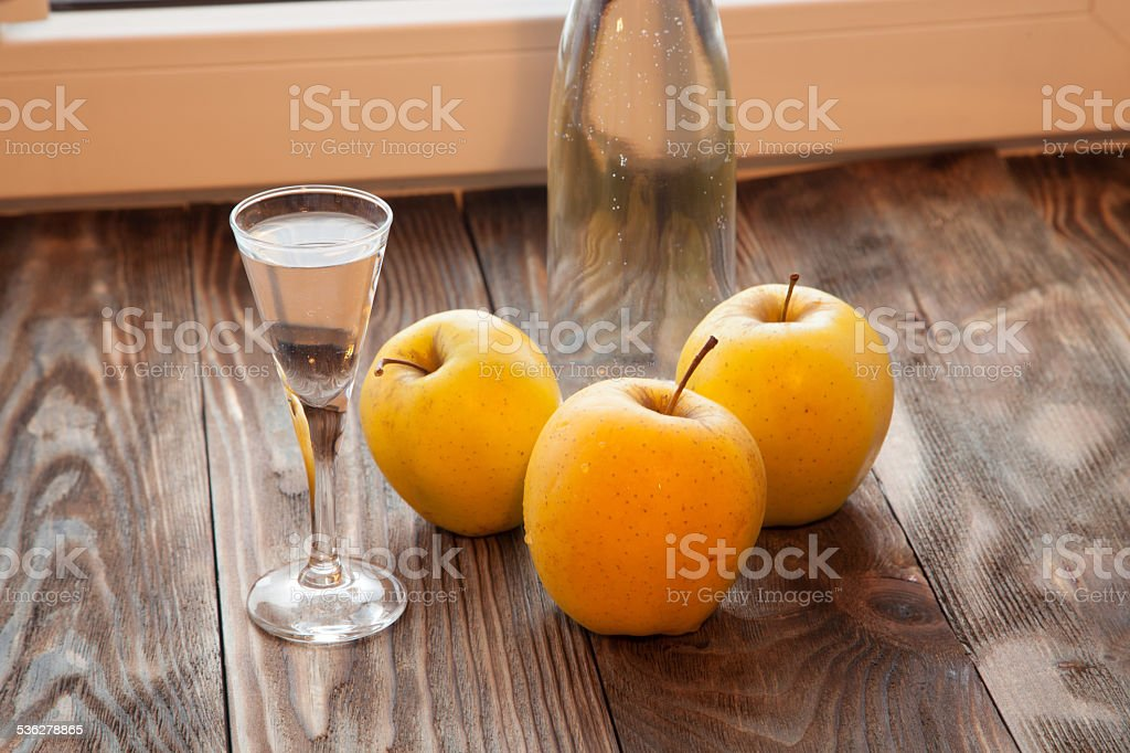 Glass with Calvados brandy and yellow apples stock photo