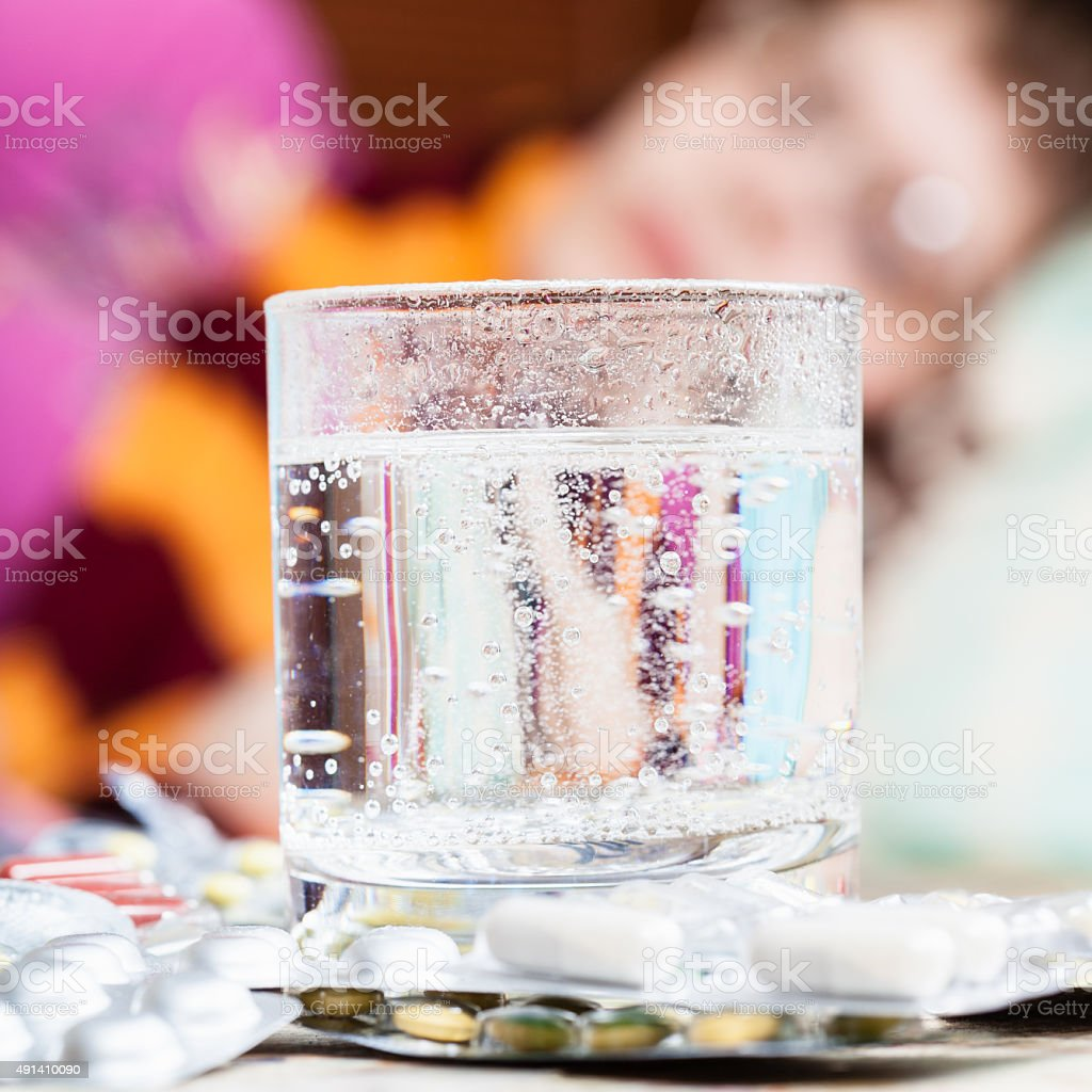 glass with dissolved drug in and pills on table stock photo
