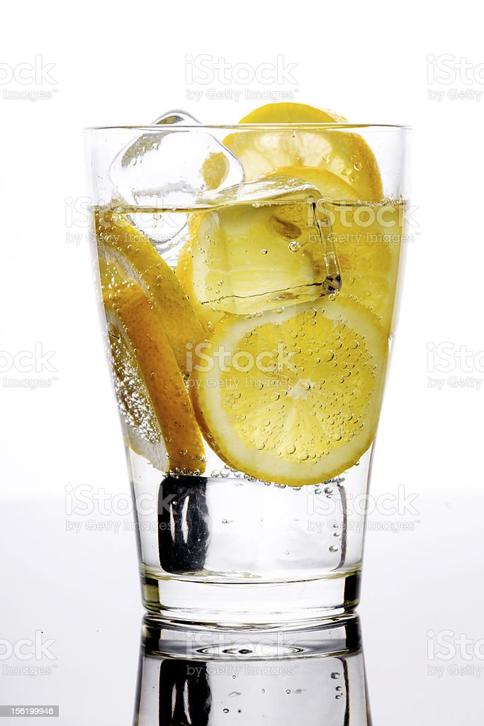 Glass with fizzy liquid and lemon slice royalty-free stock photo