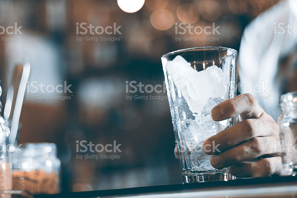 Glass with ice cubes on the background of the bar stock photo