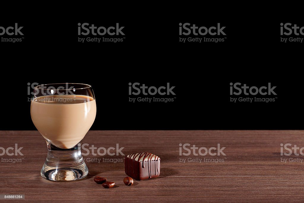 Glass with liquor, candy and coffee beans. Black background. stock photo