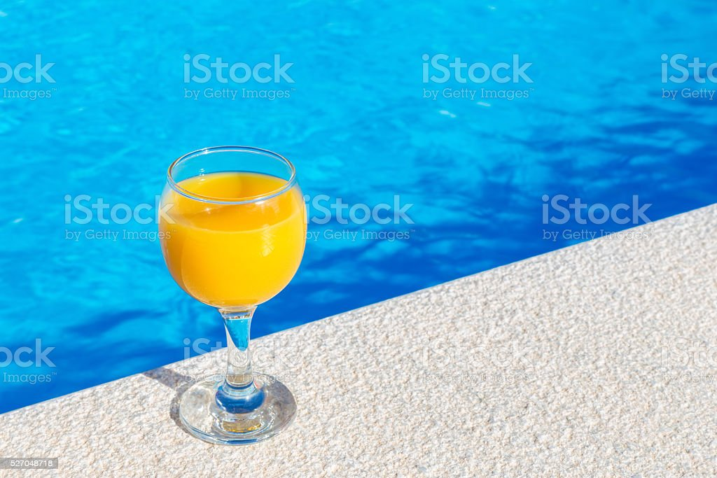 Glass with orange juice on edge of swimming pool stock photo