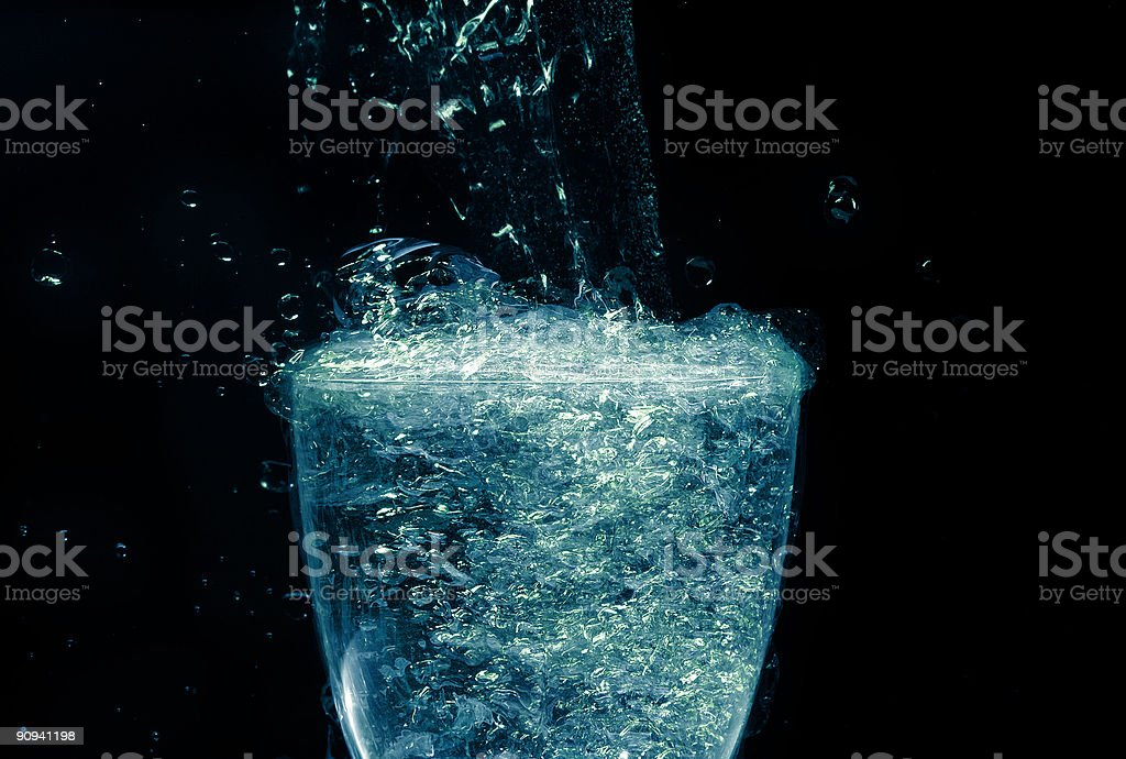 Glass with overflowing brilliant liquid stock photo