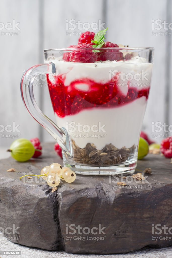 glass with raspberries, granola and yogurt arranged in layers closeup stock photo