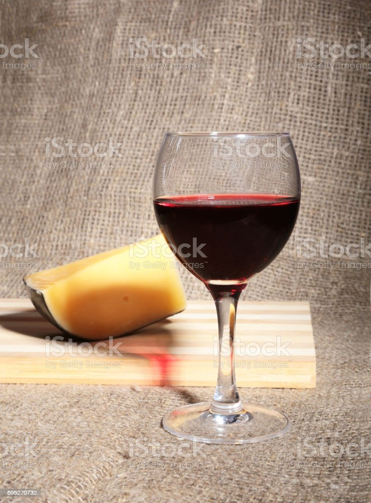 Glass with red wine grapes and chees on wooden table. stock photo