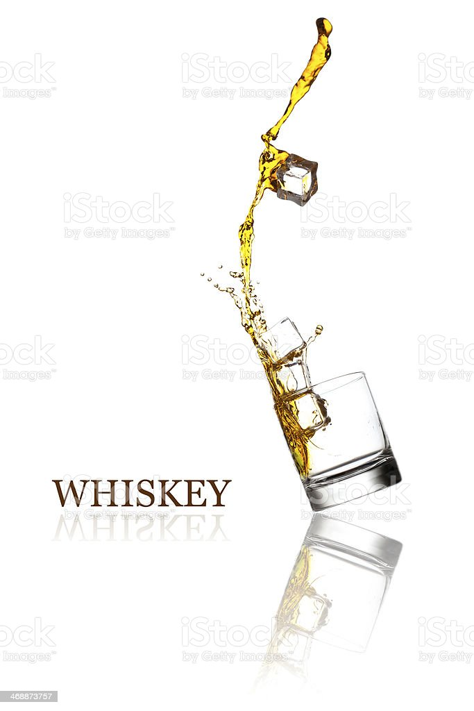 Glass with splashing whisky drink. Isolated on a white background stock photo