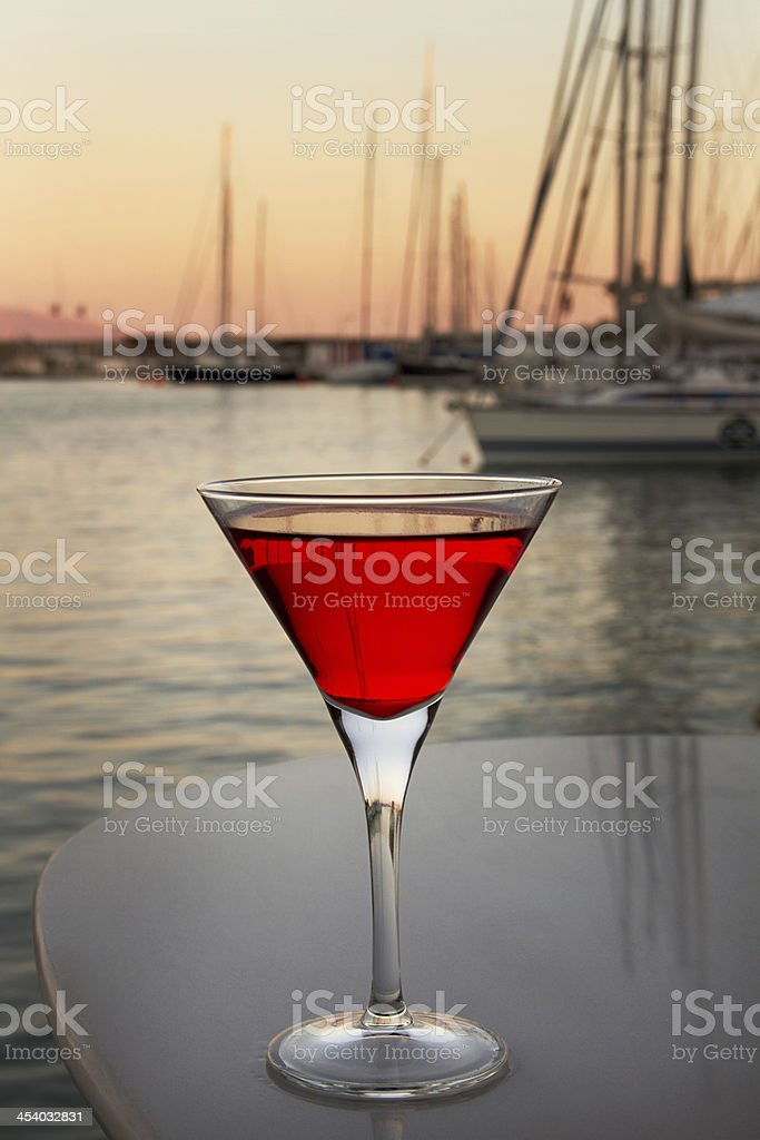 glass with the red cocktail on  background sea and boats royalty-free stock photo