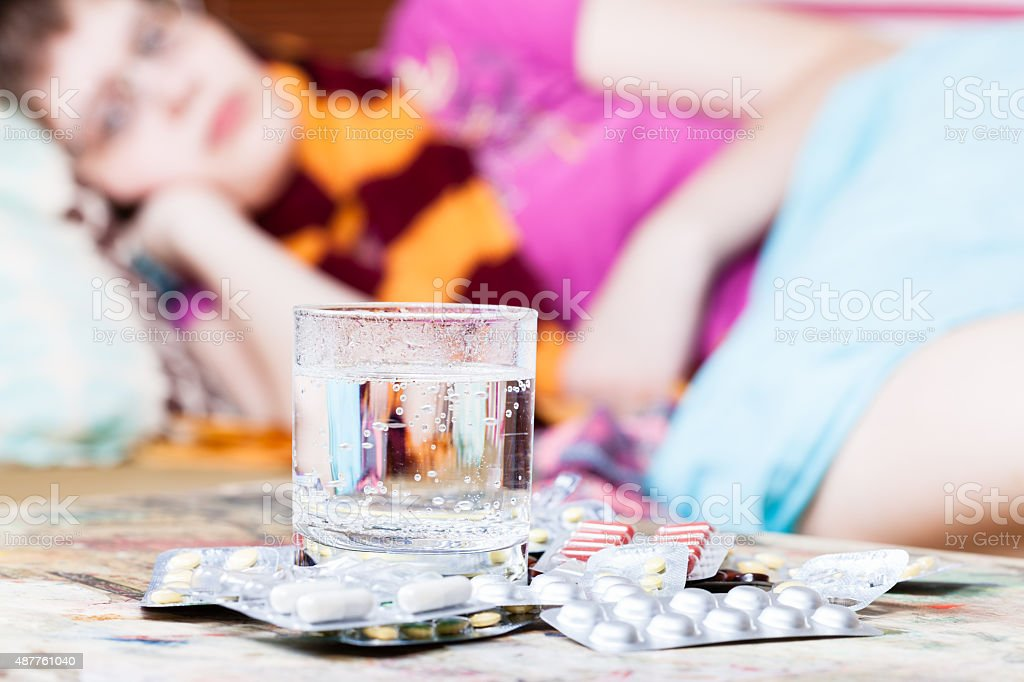 glass with water and pills close up and sick girl stock photo