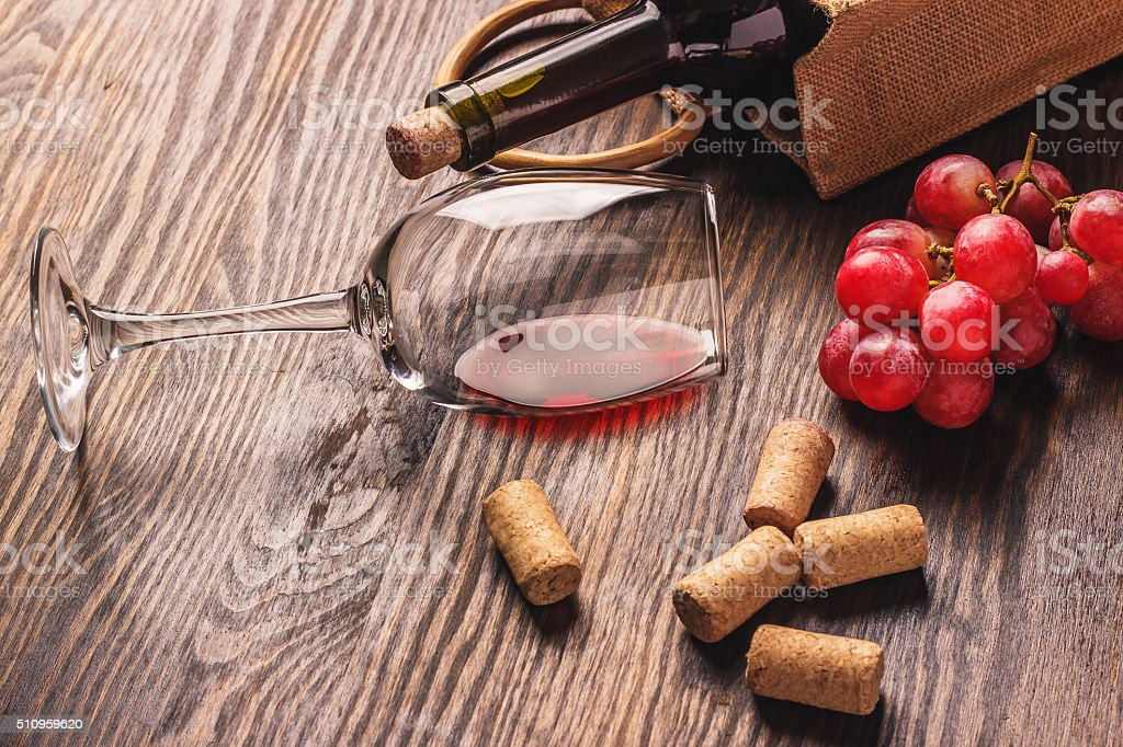 Glass with wine, bottle and bunch of grapes, wooden background stock photo