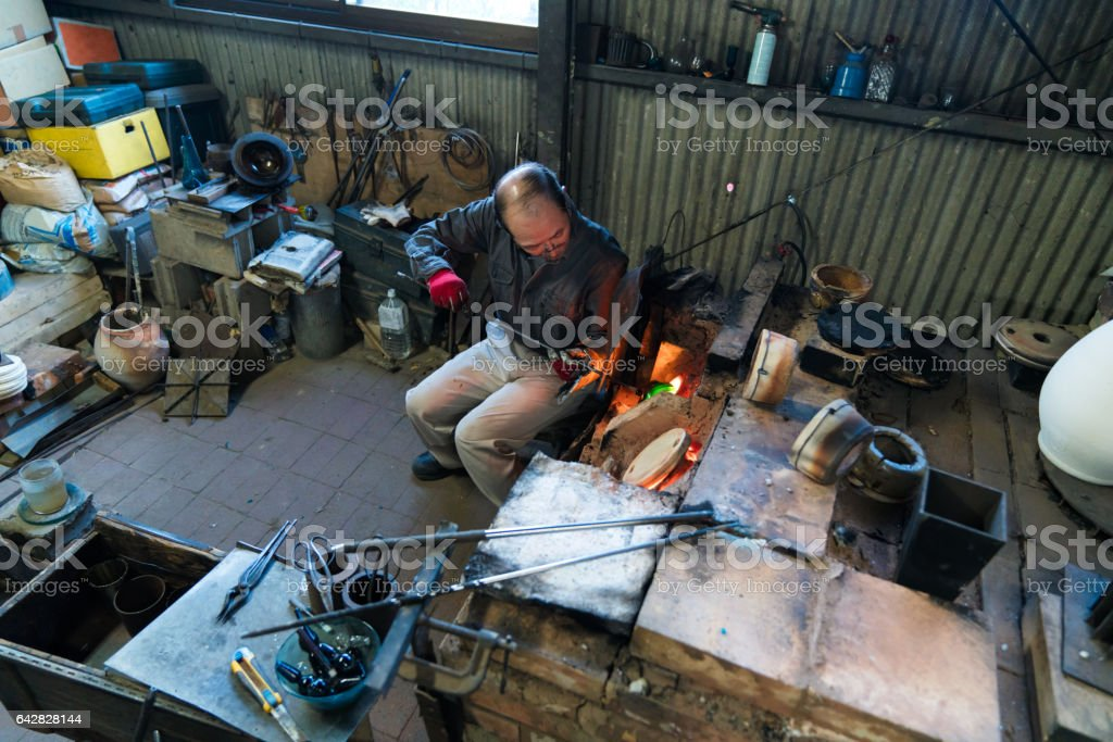 Glassblower heating his glass in a kiln stock photo