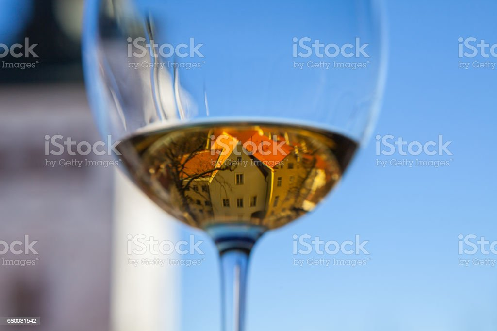 Glasse of white wine with old Tallinn view in reflection stock photo