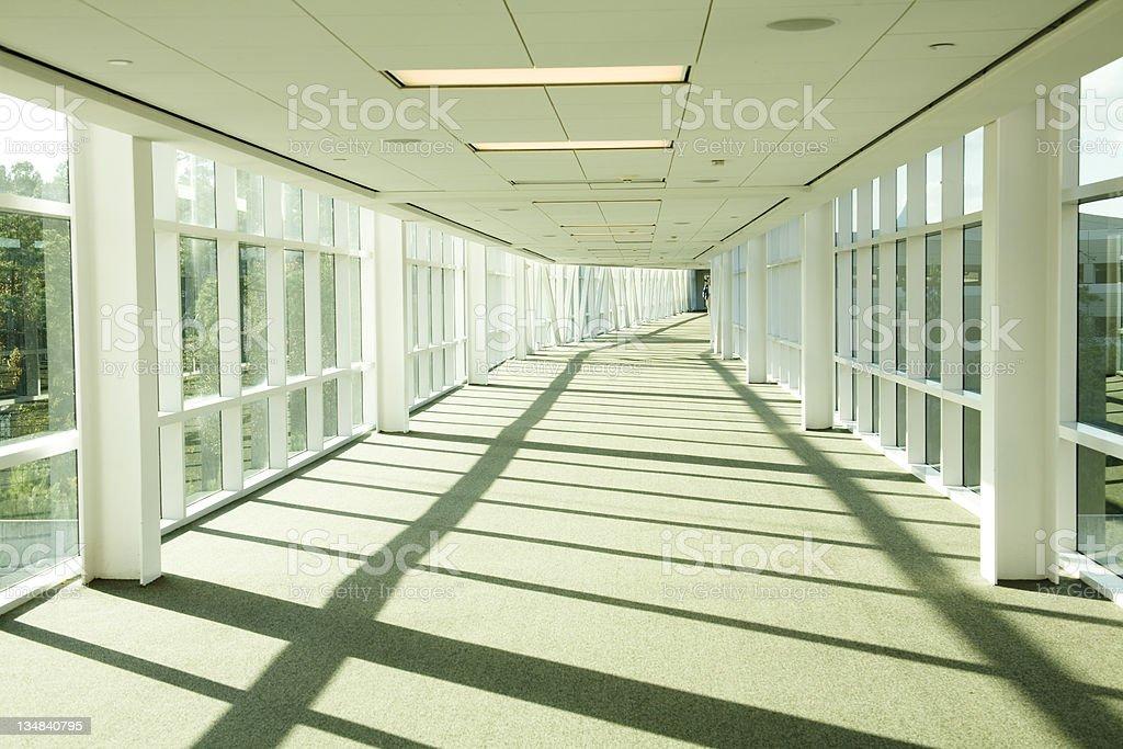 Glassed-in elevated walkway. Hallway, bright, bridge. Nobody. Office, hotel. royalty-free stock photo