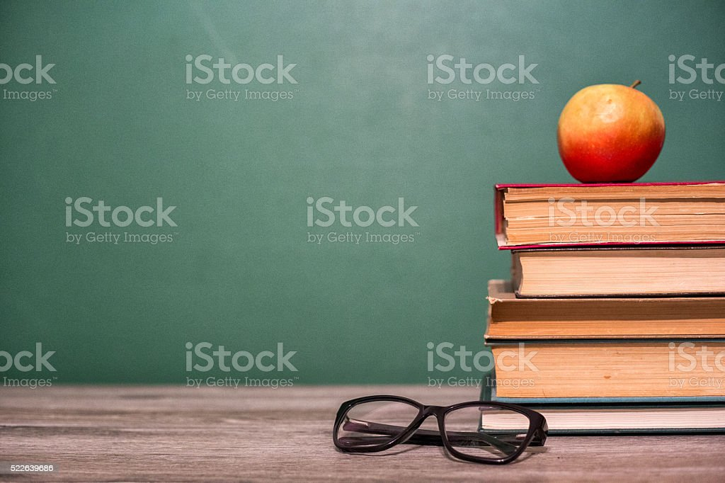 Glasses and apple on a pile of books. stock photo