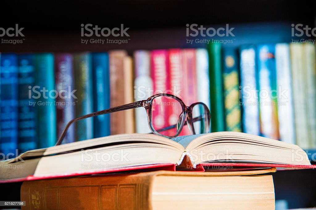 glasses and book on background bookcase stock photo