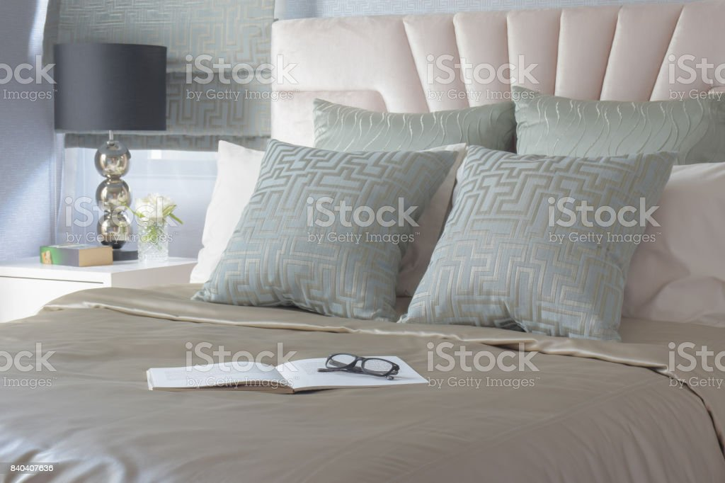 Glasses and book on bed with satin style bedding