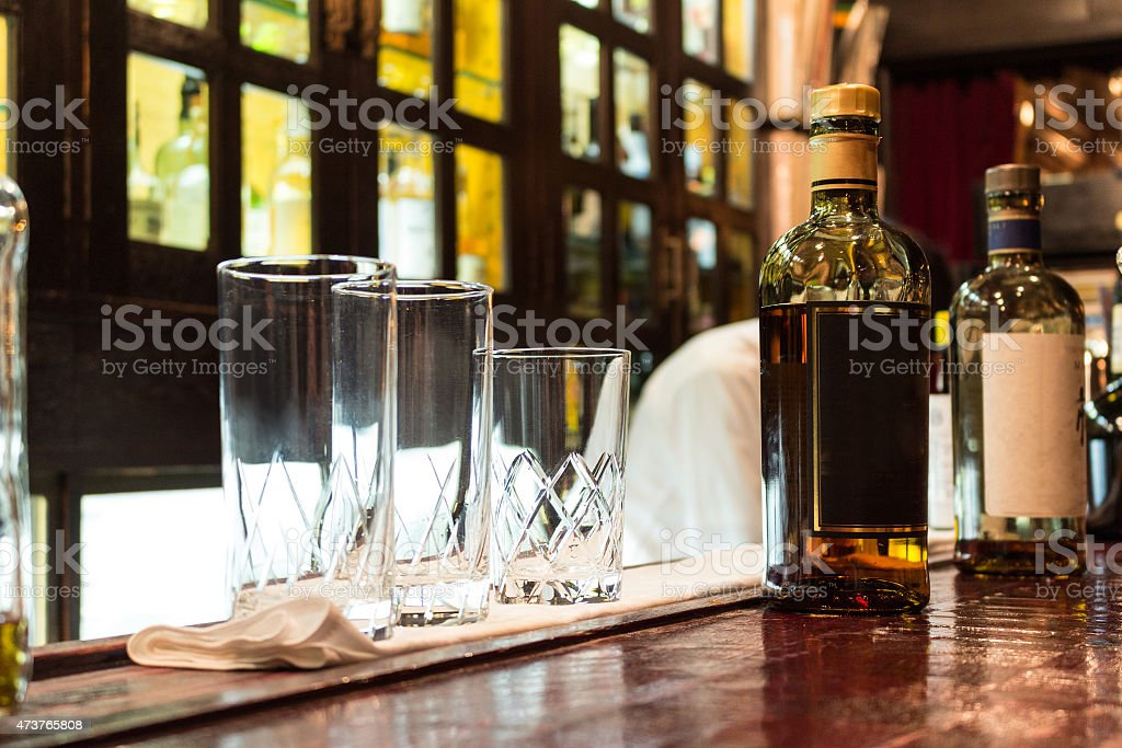 glasses and bottles of whiskey on the bar counter stock photo