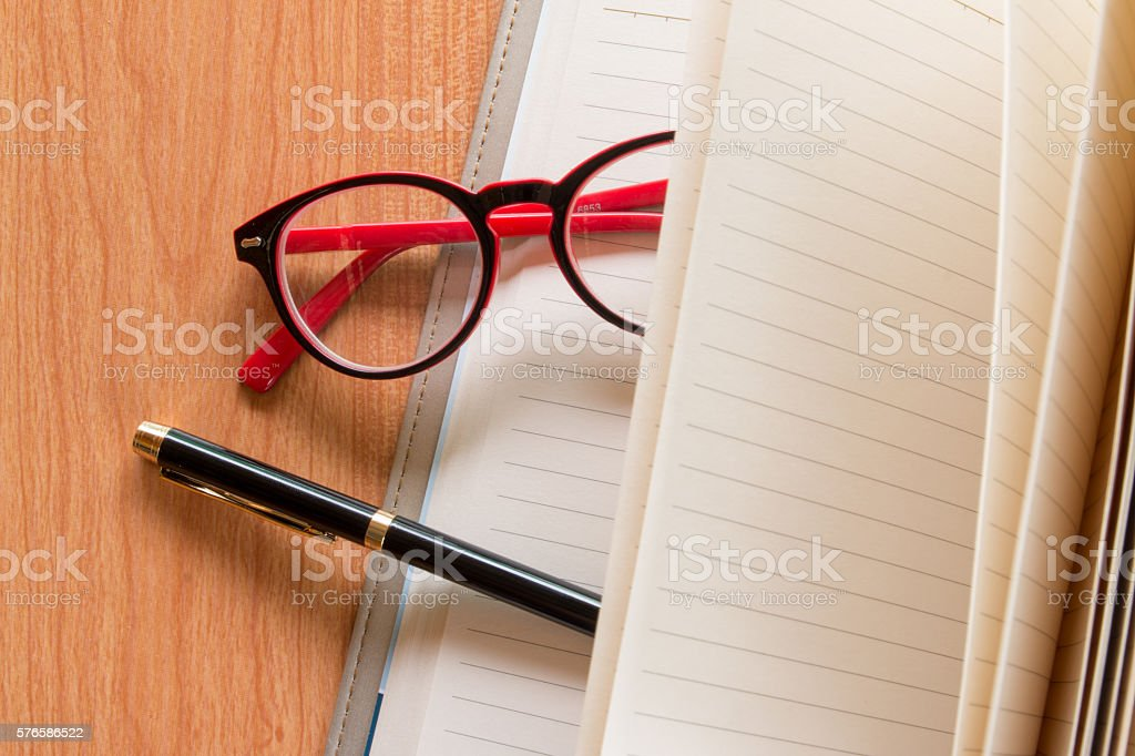 glasses and pen on open notebook stock photo
