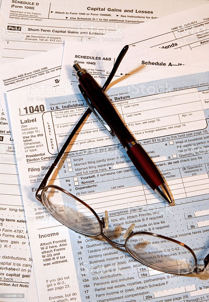 Glasses and pen over tax documents royalty-free stock photo