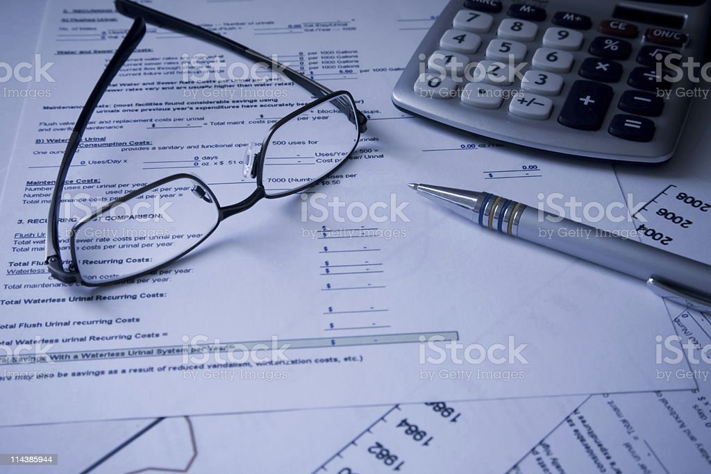 Glasses, calculator and pen on Financial cost documents stock photo