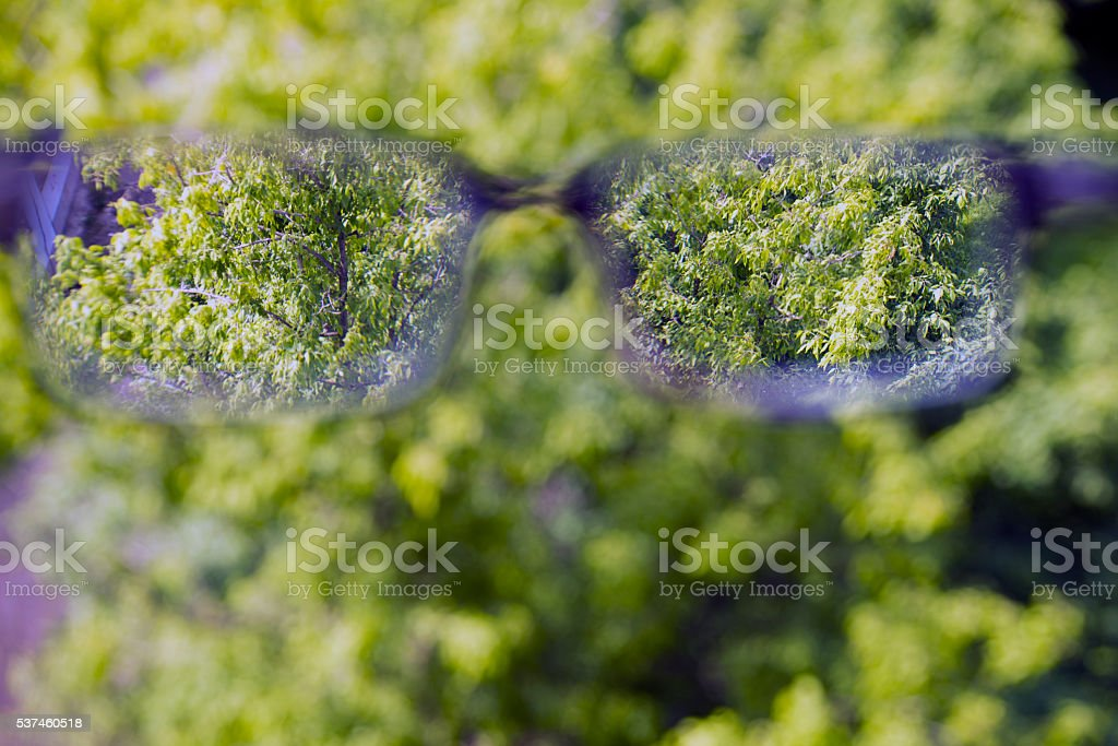 Glasses, eyeglasses in the hand over blurred background stock photo