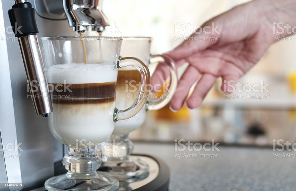 Glasses filled with capuccino in coffee machine, womans hand royalty-free stock photo