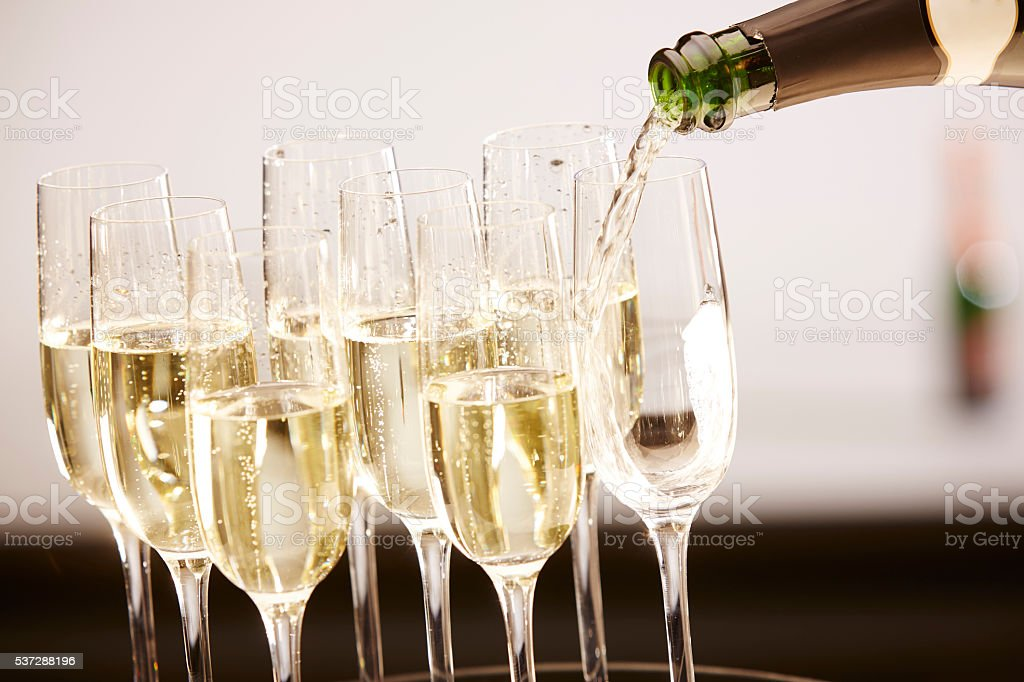 Glasses full of champagne on a tray stock photo