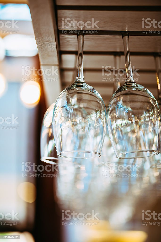 Glasses hanging above bar rack. stock photo