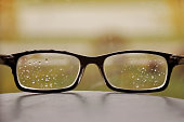 Glasses in a black frame with raindrops on the lens.