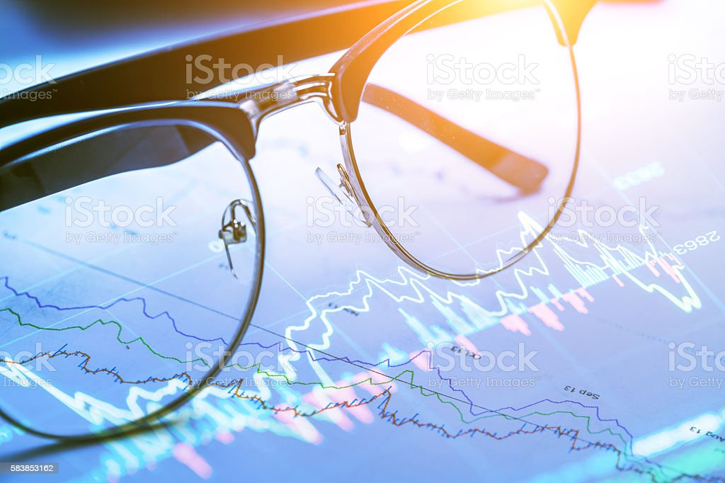glasses  in office with stock market data stock photo